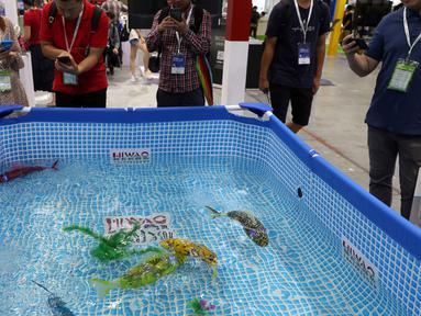 Pengunjung melihat ikan robot buatan Hiwao saat China International Robot Show di Shanghai (10/7/2019). Pameran yang menghadirkan robot-robot canggih ini diselenggarakan dari 10 sampai 13 Juli 2019. (AFP Photo/STR)