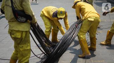 Petugas Bina Marga merapikan kabel optik yang baru saja dipotong di sepanjang jalan kawasan Kemang, Jakarta, Kamis (24/10/2019). Pemotongan kabel optik tersebut untuk menertibkan instalasi kabel yang semrawut serta mengganggu ketertiban umum di kawasan Kemang. (Liputan6.com/Immanuel Antonius)