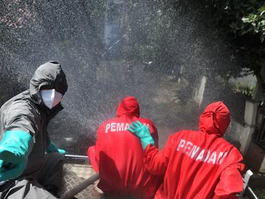 Petugas pemadam kebakaran Ciganjur menyemprotkan disinfektan di kawasan RW 015, Srengseng Sawah, Jakarta, Sabtu (26/12/20220). Setiap harinya, petugas Damkar ini berkeliling memenuhi permintaan warga untuk menyemprotkan disinfektan guna memutus penyebaran Covid-19. (merdeka.com/Arie Basuki)