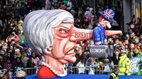 Karakter yang menggambarkan Perdana Menteri Inggris Theresa May dengan hidung panjang bertulis 'brexit' memeriahkan Karnaval Rose Monday di Duesseldorf, Jerman, Senin (4/3). (AP Photo/MartinMeissner)