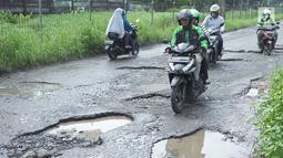 Pengendara sepeda motor berusaha menghindari jalan yang rusak di Jalan Raya Gas Alam, Depok, Jawa Barat, Selasa (7/5). Kondisi jalan yang tidak kunjung diperbaiki tersebut menjadi kubangan air setiap hujan serta berbahaya bagi keselamatan pengguna jalan. (Liputan6.com/Immanuel Antonius)