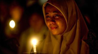 Umat muslim meneteskan air mata ketika mengikuti doa bersama lintas agama saat peringatan setahun tragedi bom gereja Surabaya di luar Gereja Katolik Santa Maria Tak Bercela, Senin (13/5/2019). Pada peringatan itu digelar juga doa lintas agama yang dihadiri sejumlah pemuka agama. (Juni Kriswanto/AFP)