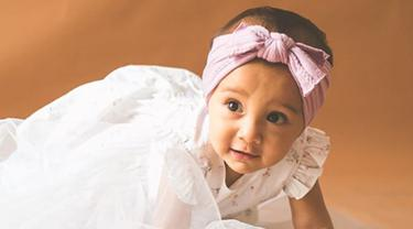 Surinala, buah hati dari pasangan Chicco Jerikho dan Putri Marino ini semakin terlihat menggemaskan dengan berbalutkan dress bewarna putih. (Liputan6.com/IG/putrimarino)