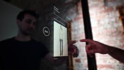 Peneliti Oak Labs, Wesley Bliss saat menggunakan cermin pintar Oak Fitting Room di sebuah butik, New York, AS (7/2). Oak Fitting Room merupakan kamar ganti yang dilengkapi cermin pintar. (AFP Photo / Jewel Samad)