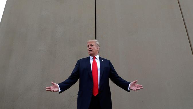 Presiden AS, Donald Trump berbincang saat melakukan perjalanan untuk melihat prototipe tembok perbatasan AS dan Meksiko di San Diego, Selasa (13/3). Tembok ini adalah perwujudan dari janji Trump pada kampanye presiden 2016 lalu. (AP/Evan Vucci)