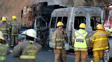 Petugas pemadam kebakaran dan forensik berada di lokasi kecelakaan antara sebuah van dan truk kargo  di jalan raya Negara Bagian Jalisco, Meksiko, Rabu (18/12/2019). (Ulises Ruiz / AFP)