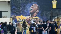 Sejumlah warga berkumpul untuk mengenang wafatnya Kobe Bryant di Staples Center, Los Angeles, Minggu (26/1). Akibat kecelakaan helikopter, legenda NBA itu wafat bersama sang putri. (AFP/Apu Gomes)