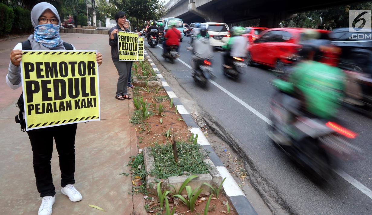 Aktivis Koalisi Pejalan Kaki melakukan aksi peduli pejalan kaki di kawasan pedestrian Kasablanka, Jakarta, Kamis (22/8). Mereka menyerukan agar tidak menggunakan trotoar sebagai tempat parkir dan berjualan.(Liputan6.com/JohanTallo)