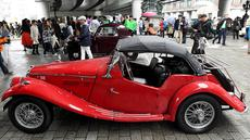 Sejumlah pengunjung melihat mobil antik dan klasik yang dipamerkan dalam acara Japan Classic Automobile 2017 di jembatan Nihonbashi di Tokyo, Jepang (9/4). (AFP/Toshifumi Kitamura