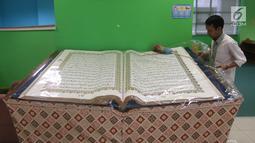 Petugas membersihkan Alquran raksasa yang dipajang di perpustakaan Jakarta Islamic Centre, Jakarta Utara, Jumat (18/5). Alquran ini memiliki ukuran 100 cm x 50 cm dengan berat mencapai 100 kilogram. (Liputan6.com/Arya Manggala)