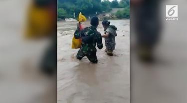 Aksi terpuji dilakukan tentara penjaga perbatasan Indonesia-Timor Leste, membantu warga melintasi sungai yang sedang meluap.