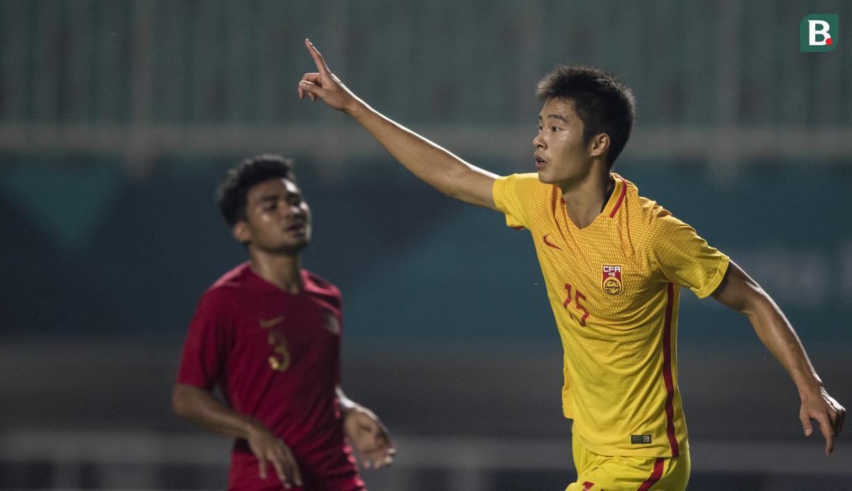 Bek China, Wang Jinze, merayakan gol yang dicetaknya ke gawang Timnas Indonesia pada laga PSSI 88th U-19 di Stadion Pakansari, Jawa Barat, Selasa (25/9/2018). Indonesia kalah 0-3 dari China. (Bola.com/Vitalis Yogi Trisna)