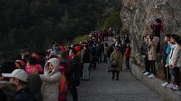 Wisatawan meyaksikan matahari terbit di Niu Yu, Xiapu, Provinsi Fujian, China, Jumat (13/12/2019). Xiapu menjadi daya tarik tersendiri bagi fotografer pemula karena jauh dari gedung pencakar langit dan hiruk pikuk kota-kota besar di China. (RETAMAL HECTOR/AFP)