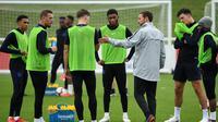 Pelatih Inggris Gareth Southgate berbicara dengan pemain selama sesi latihan di St George's Park di Burton-on-Trent, Inggris tengah (4/9). Inggris akan bertanding melawan Spanyol laga persahabatan internasional 8 September. (AFP Photo/Paul Ellis)