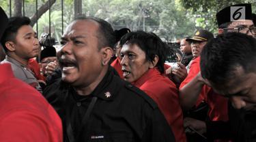 Kader PDIP Adian Napitupulu saling dorong dengan petugas saat hendak masuk ke Gedung KPU, Jakarta, Selasa (17/7). Elite serta massa PDIP terlibat kericuhan saat hendak mengantarkan pengurus DPP mendaftarkan bakal caleg. (Merdeka.com/ Iqbal S. Nugroho)