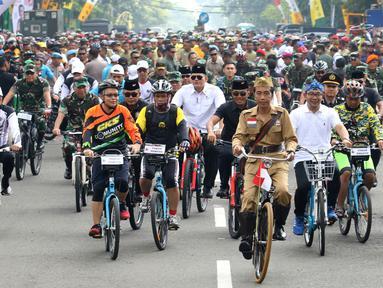 Presiden Joko Widodo atau Jokowi (tengah) didampingi Gubernur Jawa Barat Ridwan Kamil (kanan) saat mengikuti Bandung Lautan Sepeda, Sabtu (10/11). Jokowi menaiki sepeda ontel dalam kegiatan tersebut. (Liputan6.com/Angga Yuniar)