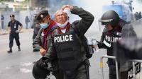 Seorang polisi bereaksi setelah gas air mata dilemparkan selama unjuk rasa anti-pemerintah di Bangkok pada 17 November 2020. (Foto: AFP / Jack Taylor)