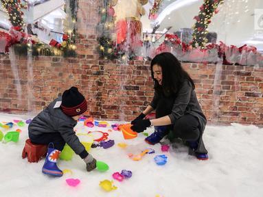 Ibu dan anak bermain salju dari es buatan di Lippo Mall Puri, Jakarta, Kamis (29/11). Wahana bermain Frosty Land di desain dengan suhu di bawah 0 derajat. (Liputan6.com/Fery Pradolo)