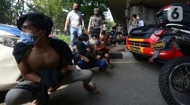 Sejumlah orang berjalan jongkok setelah diamankan petugas kepolisian di Kawasan Senayan, Jakarta, Kamis (8/10/2020). Mereka diduga hendak melakukan unjuk rasa di depan gedung DPR. (merdeka.com/Imam Buhori)