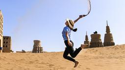 Seorang wisatawan bermain pasir di kawasan wisata Gurun Kum Tag di Wilayah Shanshan, Kota Turpan, Daerah Otonom Uighur Xinjiang, China barat laut (22/9/2020). Gurun tersebut saat ini mencatat peningkatan arus wisatawan. (Xinhua/Wang Fei)