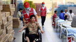 Sukarelawan mendorong kursi roda penduduk desa di tempat pengungsian sementara Sekolah Menengah No.168, Hefei, Provinsi Anhui, China, Rabu (29/7/2020). Makanan gratis, konseling psikologis, dan bantuan kehidupan sehari-hari disediakan di tempat pengungsian sementara tersebut. (Xinhua/Liu Junxi)