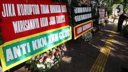Petugas keamanan mengamati sejumlah karangan bunga yang terpajang di depan PN Jakarta Pusat, Senin (12/10/2020). Karangan bunga yang mengharapkan keadilan tersebut berjejer menjelang sidang vonis terdakwa kasus dugaan korupsi di PT Asuransi Jiwasraya (Persero). (Liputan6.com/Angga Yuniar)