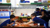 Siswa prasekolah bermain di meja besar untuk menjaga jarak selama kelas di sekolah teknik San Juan Bautista, Lambare, Paraguay, Rabu (17/2/2021). Beberapa SD swasta di Paraguay membuka kelas tatap muka minggu ini dengan protokol kesehatan ketat di tengah pandemi COVID-19. (AP Photo/Jorge Saenz)
