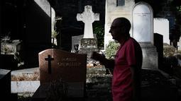 Seorang turis berjalan melewati kuburan di pemakaman Pere Lachaise di Paris (22/7/2019). Pemakaman ini jauh dari kata angker apalagi menyeramkan sebab setiap tahun ribuan bahkan jutaan wisatawan dari berbagai mancanegara berkunjung ke tempat ini. (AFP Photo/Philippe Lopez)