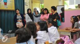 Sejumlah orang tua saat melihat anaknya belajar di hari pertama sekolah di SD Gunung 01, Jakarta, Senin (18/7). Hal ini untuk mencegah tindak kekerasaan dan perploncoan di sekolah pada saat masa orientasi atau pengenalan. (Liputan6.com/Gempur M Surya)
