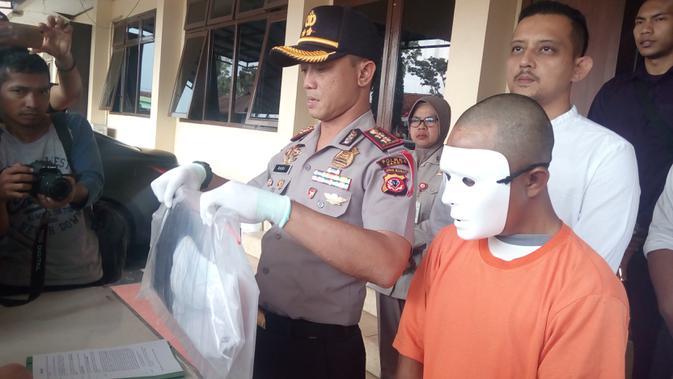 Kapolres Garut AKBP Budi Satria Wiguna menunjukan pelaku pencabulan terhadap anak kandungnya di Garut (Liputan6.com/Jayadi Supriadin)