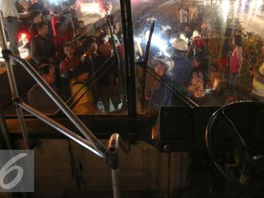 Sejumlah warga mengerumuni pria tanpa identitas yang sekarat usai di tabrak bus PPD 213 di kawasan Matraman Raya, Jakarta, Kamis (20/8/2015). Menurut saksi pria tersebut nekat menyeberang melewati jalur busway. (Liputan6.com/Faizal Fanani)