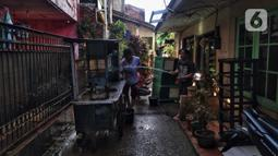 Warga membersihkan gerobak usai banjir di Kebalen, Jakarta, Minggu (21/2/2021). Banjir yang terjadi kemarin karena curah hujan yang tinggi meninggalkan sampah di rumah warga. (Liputan6.com/Johan Tallo)