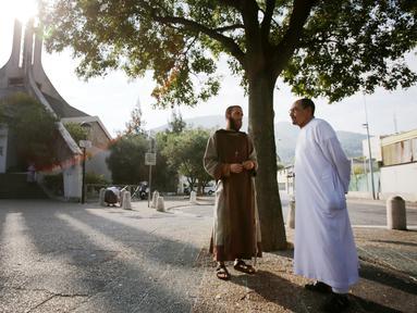 Pastor dan imam Muslim berbincang di depan gereja Saint-Pierre-de-l'Ariane di Nice, Prancis, Minggu (31/7). Muslim di penjuru Prancis menghadiri misa sebagai solidaritas atas pembunuhan seorang pastor oleh militan Islam. (Jean Christophe MAGNENET/AFP)