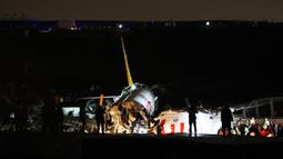 Tim penyelamat bekerja setelah sebuah pesawat tergelincir di landasan pacu Bandara Sabiha Gokcen, Istanbul, Turki, Rabu (5/2/2020). Pihak berwenang mengatakan sebanyak 52 orang terluka dalam kejadian tersebut. (AP Photo)