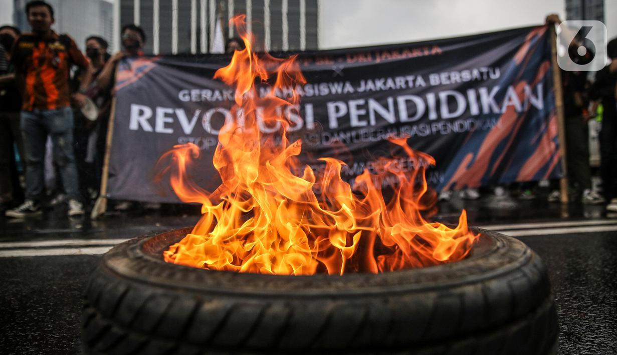 Massa yang tergabung dalam Gerakan Mahasiswa Jakarta Bersatu membakar ban saat unjuk rasa di depan gedung Kementerian Pendidikan dan Kebudayaan, Jakarta, Kamis (2/7/2020). Mereka menuntut adanya keringanan uang tunggal kuliah (UKT) sebesar 50 persen di tengah pandemi. (Liputan6.com/Faizal Fanani)