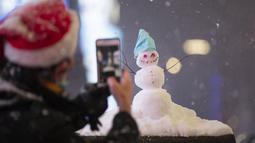 Seorang pria mengabadikan foto manusia salju di Times Square, New York, Amerika Serikat (16/12/2020). Suhu yang sangat dingin, angin kencang, dan hujan es membuat kondisi menjadi lebih buruk. (Xinhua/Wang Ying)