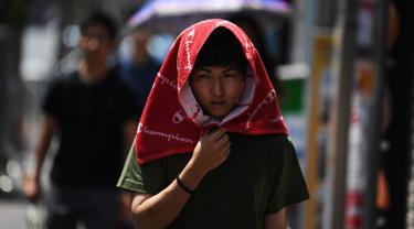 Seorang pria melindungi dirinya dari sinar matahari dengan handuk yang menutupi kepala selama gelombang panas di distrik Shin-Okubo Tokyo pada Minggu (4/8/2019). Setelah menyerang beberapa wilayah di Eropa, suhu tinggi juga terjadi di Jepang. (Charly TRIBALLEAU / AFP)