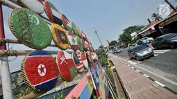 Instalasi berupa bendera negara-negara peserta Asian Games 2018 terlihat di Jalan Tanah Tinggi Barat, Jakarta, Minggu (15/7). Kelurahan Bungur juga memasang bendera 45 negara peserta Asian Games yang terbuat dari tampah. (Merdeka.com/Iqbal S. Nugroho)