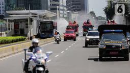 Mobil pemadam dari Dinas Pemadam Kebakaran Pemprov DKI melakukan penyemprotan cairan disinfektan di Jalan Thamrin, Jakarta, Selasa (31/3/2020). Penyemprotan yang dilakukan terus menerus itu untuk meminimalisir penyebaran COVID-19 di ruang udara dan ruas jalan. (Liputan6.com/Faizal Fanani)