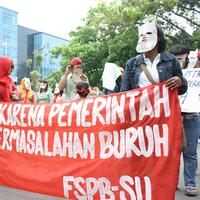 Potret para buruh yang turun ke jalan untuk menuntut hak-hak mereka.