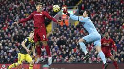 Penyerang Liverpool, Roberto Firmino, berebut bola dengan kiper Southampton, Alex McCarthy, pada laga Premier League di Stadion Anfield, Sabtu (1/2/2020). Liverpool menang 4-0 atas Southampton. (AP/Jon Super)