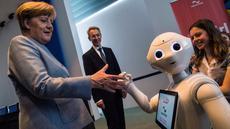 Kanselir Jerman Angela Merkel disapa robot interaktif di stand digitalSTROM selama pameran Girl's Day di Berlin, Rabu (26/4). Pameran ini bertujuan menarik wanita muda untuk menggeluti pekerjaan hi-tech dan engineering. (AFP PHOTO / John MACDOUGALL)