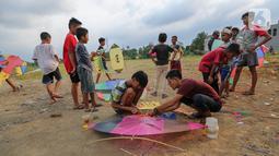 Anak-anak bersiap menerbangkan layangan koang di lahan kosong Kampung Sawah, Ciputat, Tangerang Selatan, Selasa (2/6/2020). Masa pembatasan sosial berskala besar selama pandemi Covid-19 tidak menyurutkan anak-anak bermain layangan koang meski tanpa menggunakan masker. (Liputan6.com/Fery Pradolo)