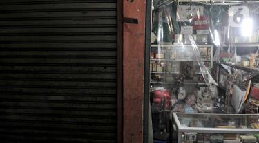 Pedagang tertidur saat menunggu pembeli selama pemberlakukan ganjil genap pasar tradisional di Jakarta, Senin (15/6/2020). Hari ini PD Pasar Jaya memberlakukan penerapan ganjil genap di pasar tradisional sebagai upaya membatasi jumlah pengunjung selama PSBB transisi. (merdeka.com/Iqbal S. Nugroho)