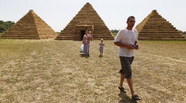 Wisatawan berjalan di sekitar replika Piramida Giza yang terbuat dari jerami di permukiman Krasnoye, Rusia, Rabu (19/7). Piramida unik itu salah satu bangunan yang menghiasi taman jerami di wilayah pertanian Ponomaryovo. (REUTERS/Eduard Korniyenkov)