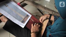 Warga menyelesaikan pembuatan tenun bertema Monas saat Pelatihan Tenun Betawi di Rusun Jatinegara Barat, Jakarta, Rabu (6/11/2019). Dekranasda DKI Jakarta memberikan Pelatihan Tenun Betawi kepada warga rusun Jatinegara Barat sejak 29 Oktober-20 November 2019. (merdeka.com/Iqbal Nugroho)