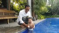Jokowi temani cucu pertamanya Jan Ethes main air. (Foto: Youtube/Presiden Joko Widodo)