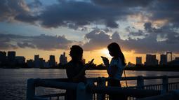 "Dua wanita bermain ponsel mereka saat matahari terbenam di Odaiba, Tokyo, (29/7). Nama ""Odaiba"" berasal dari sebutan untuk enam pulau di Teluk Tokyo yang dibangun sebagai benteng oleh Keshogunan Tokugawa. (AFP Photo/Martin Bureau)"