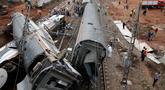 Orang-orang berkumpul setelah sebuah kereta api keluar jalur dan terguling di Sidi Bouknadel dekat ibu kota Rabat, Maroko, Selasa (16/10). Akibat insiden ini, 6 penumpang tewas dan puluhan lainnya mengalami luka-luka. (AP/Abdeljalil Bounhar)