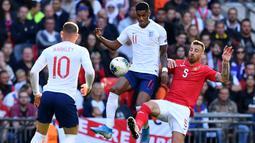 Striker Inggris, Marcus Rashford, berebut bola dengan bek Bulgaria, Nikolay Bodurov, pada laga Kualifikasi Piala Eropa 2020 di Stadion Wembley, London, Sabtu (7/9). Inggris menang 4-0 atas Bulgaria. (AFP/Ben Stansall)